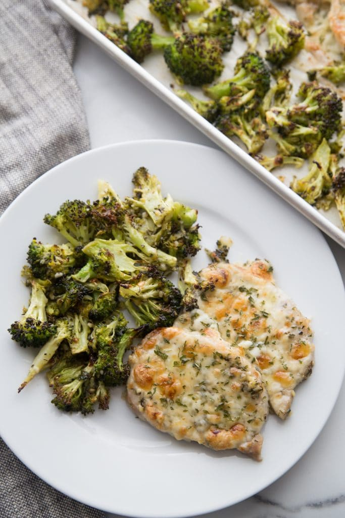 keto oven baked pork chops recipe with broccoli plated with sheet pan in the background