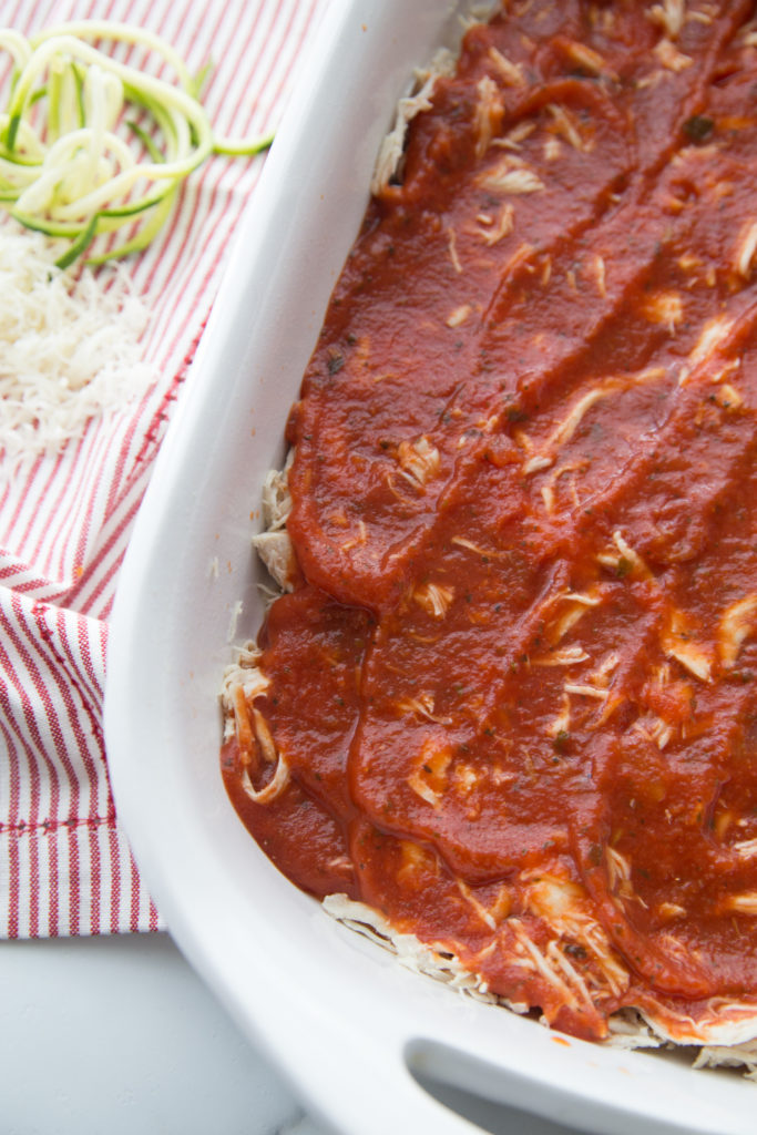 shredded chicken and low carb marinara sauce layered in a casserole dish for keto chicken parmesan casserole
