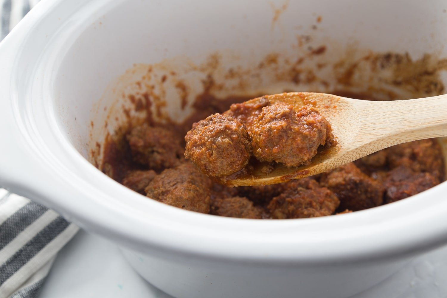 meatballs coated in bbq sauce in a crock-pot with a large wooden spoon scooping the out