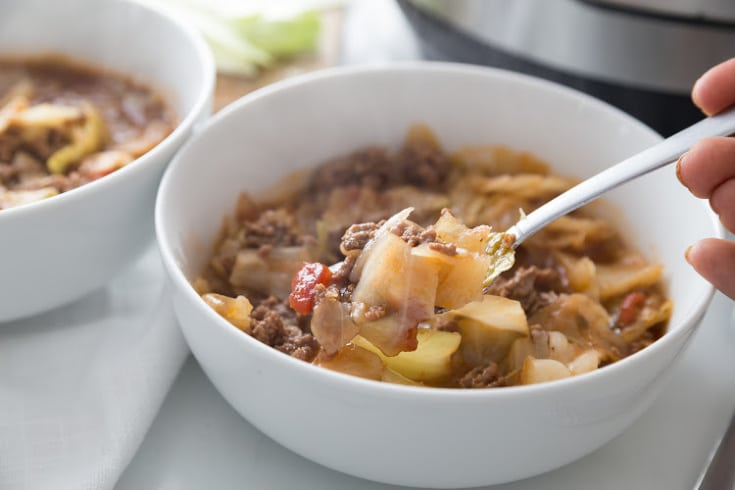 unstuffed cabbage soup in a white bowl with a bite on a spoon