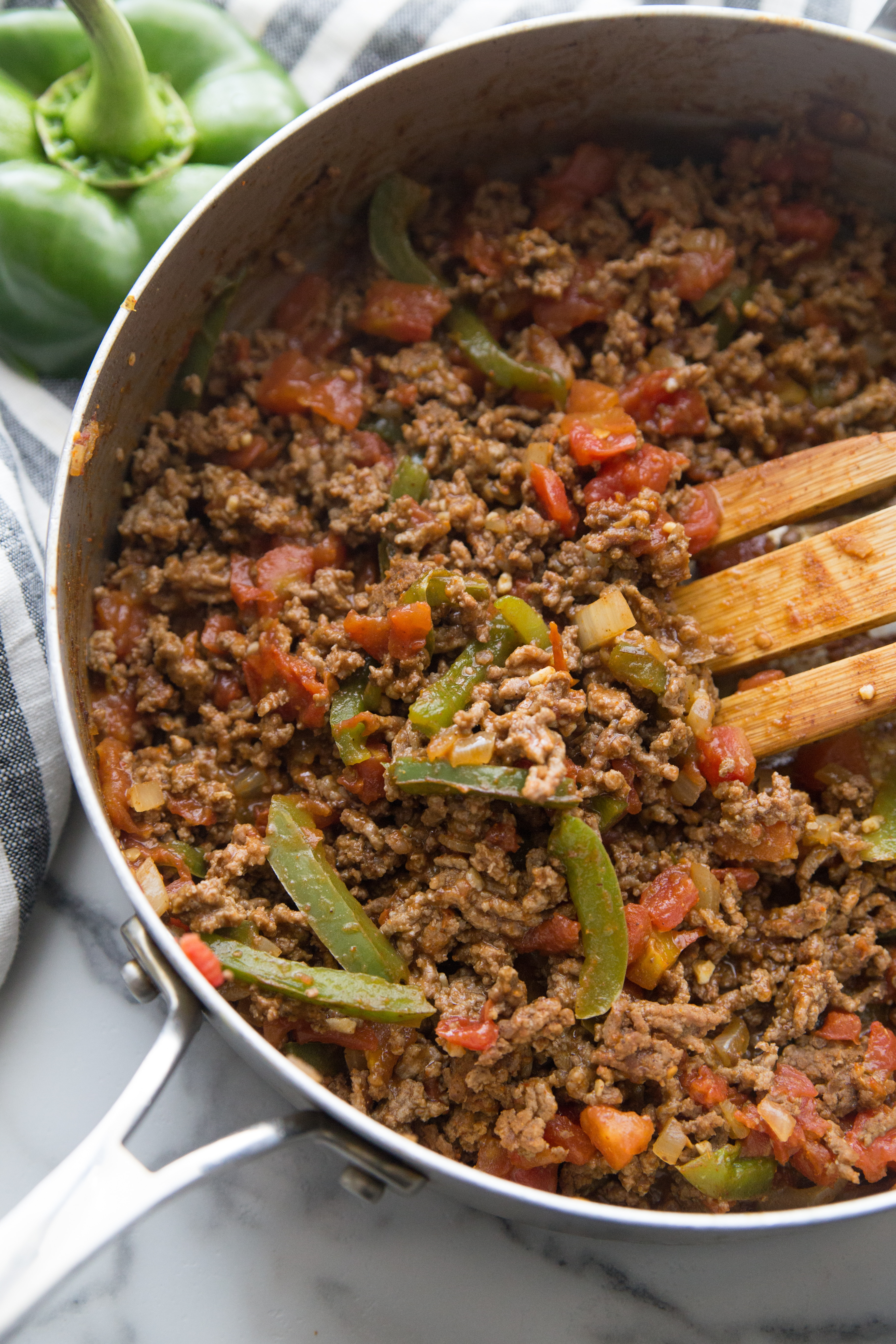 ground taco meat in a skillet with ro-tel tomatoes, taco seasoning and veggies
