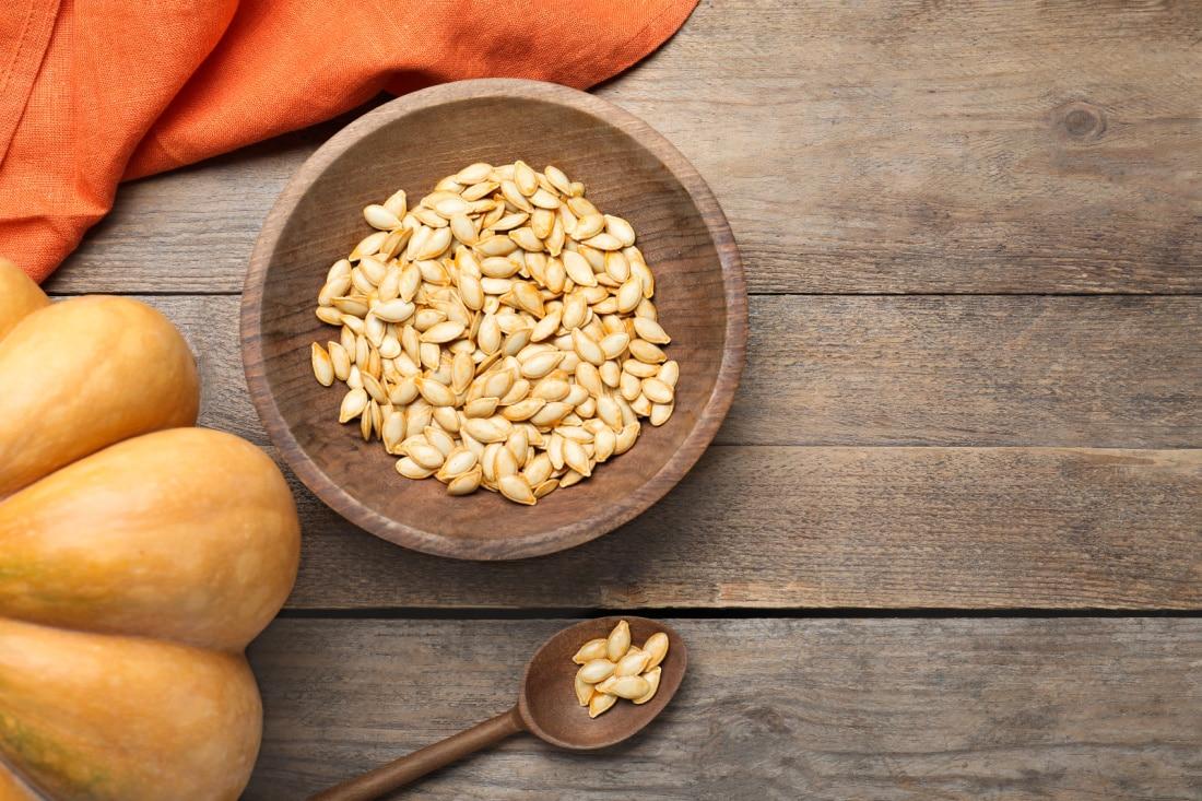 raw pumpkin seeds in a wooden bowl