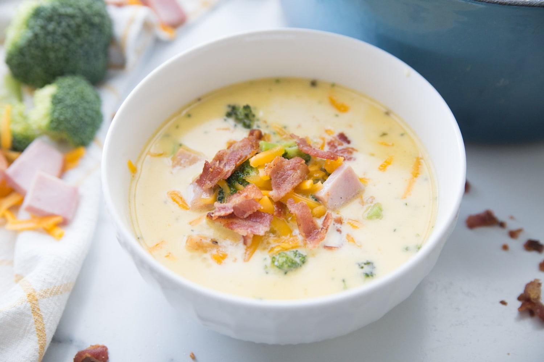 cheesy ham chowder in a white bowl