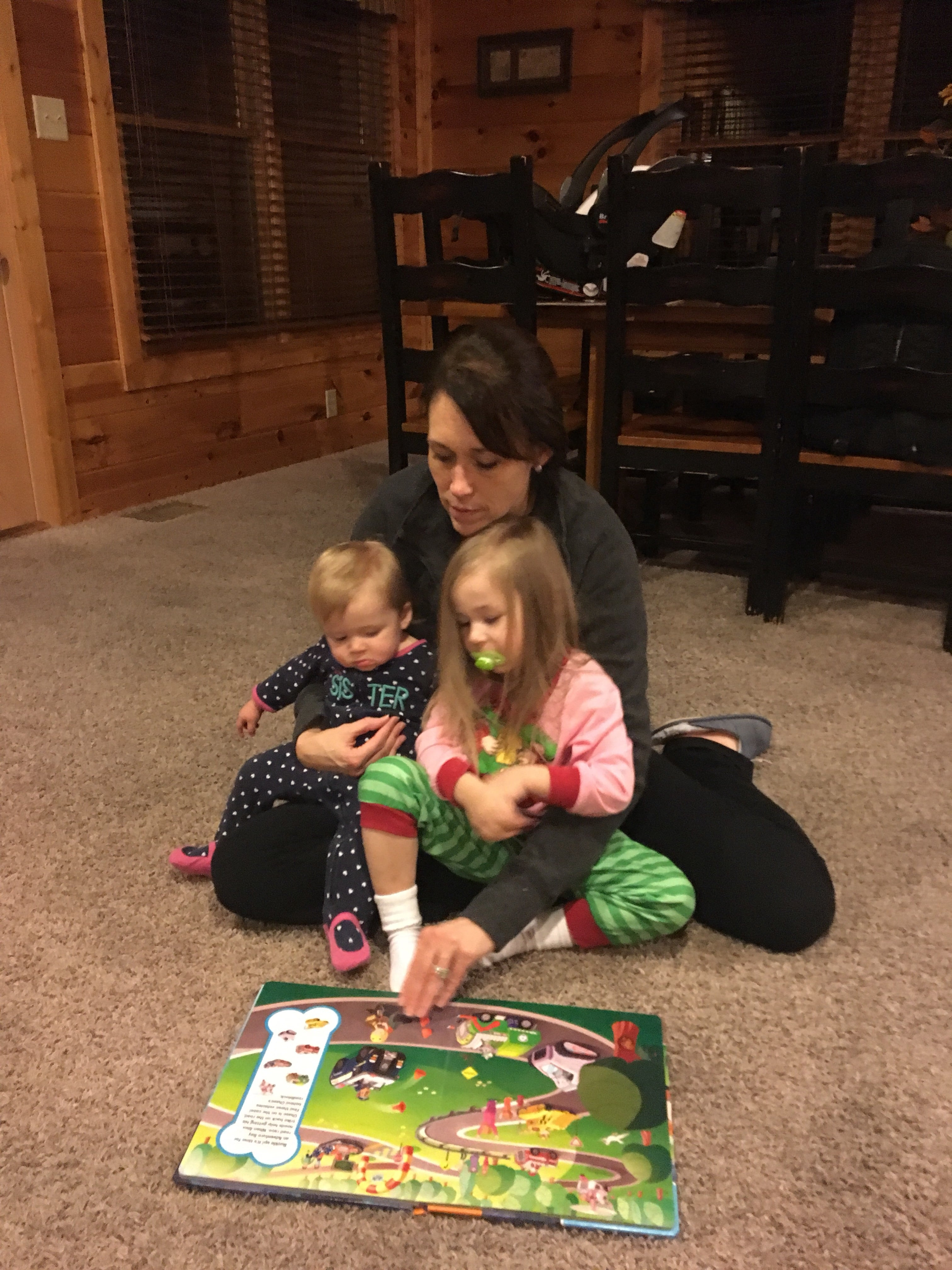 mom reading a book to toddlers