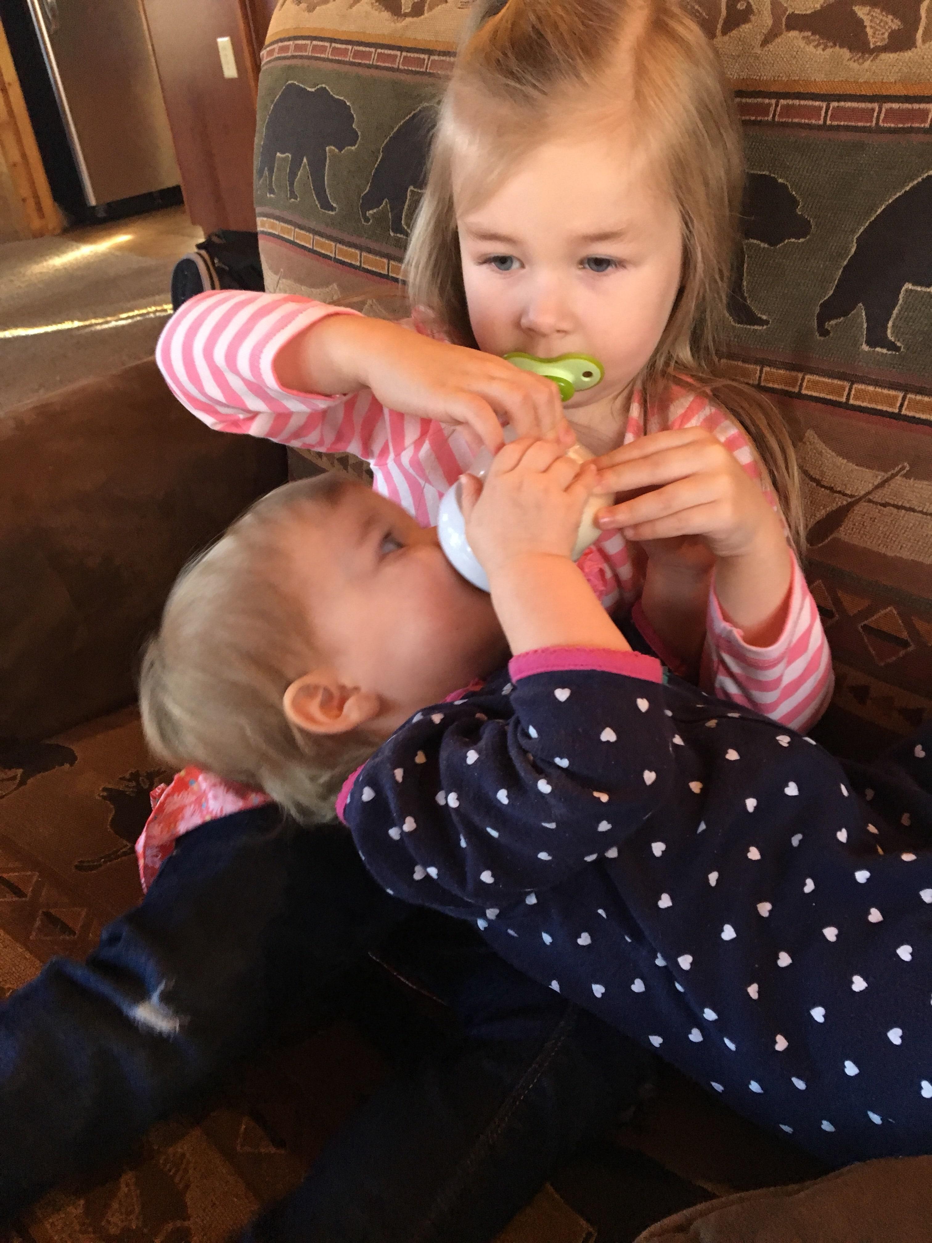 sister holding baby sisters bottle