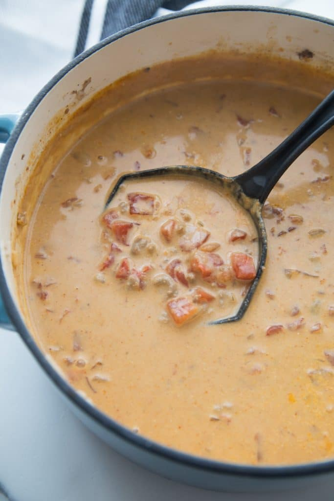 queso keto soup in a dutch oven being scooped out