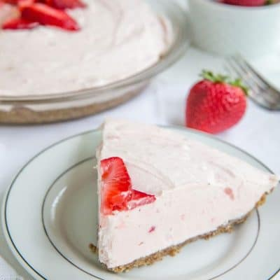keto strawberry pie on a white plate with pie plate in background