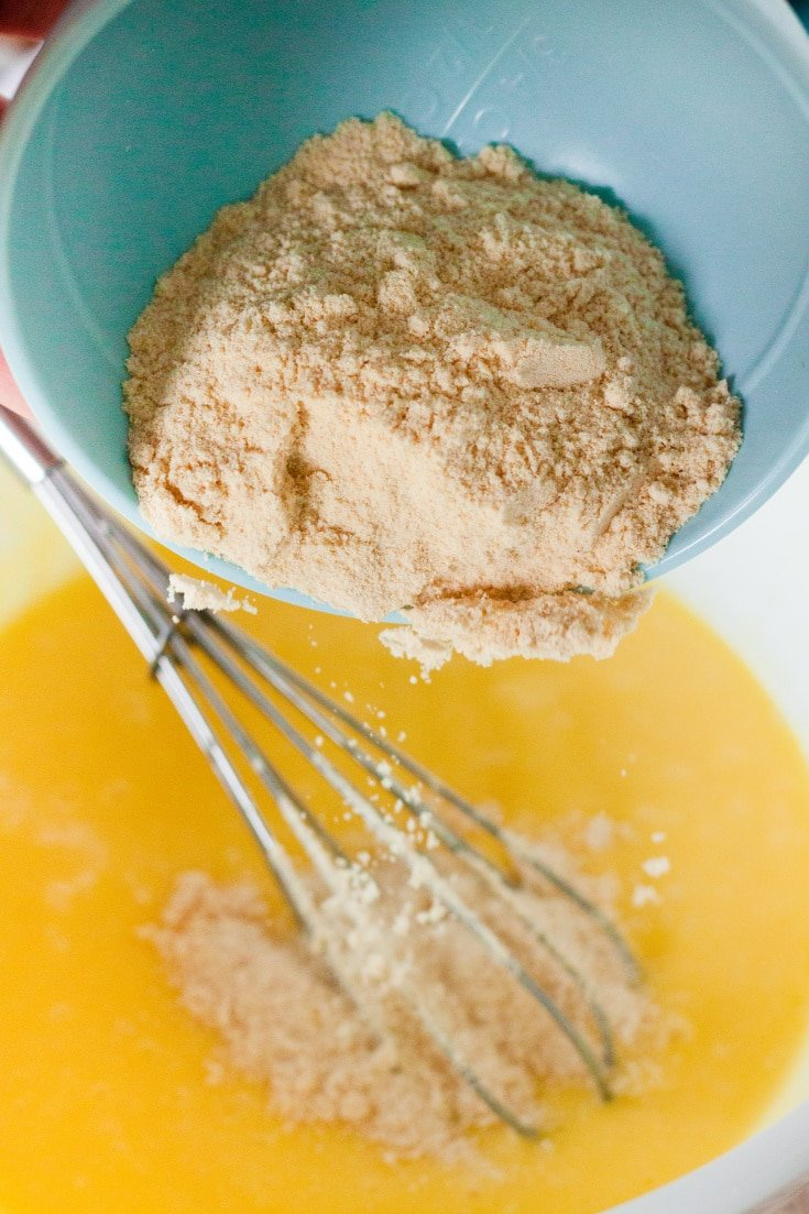 small bowl dumping coconut flour into larger bowl with eggs/melted butter