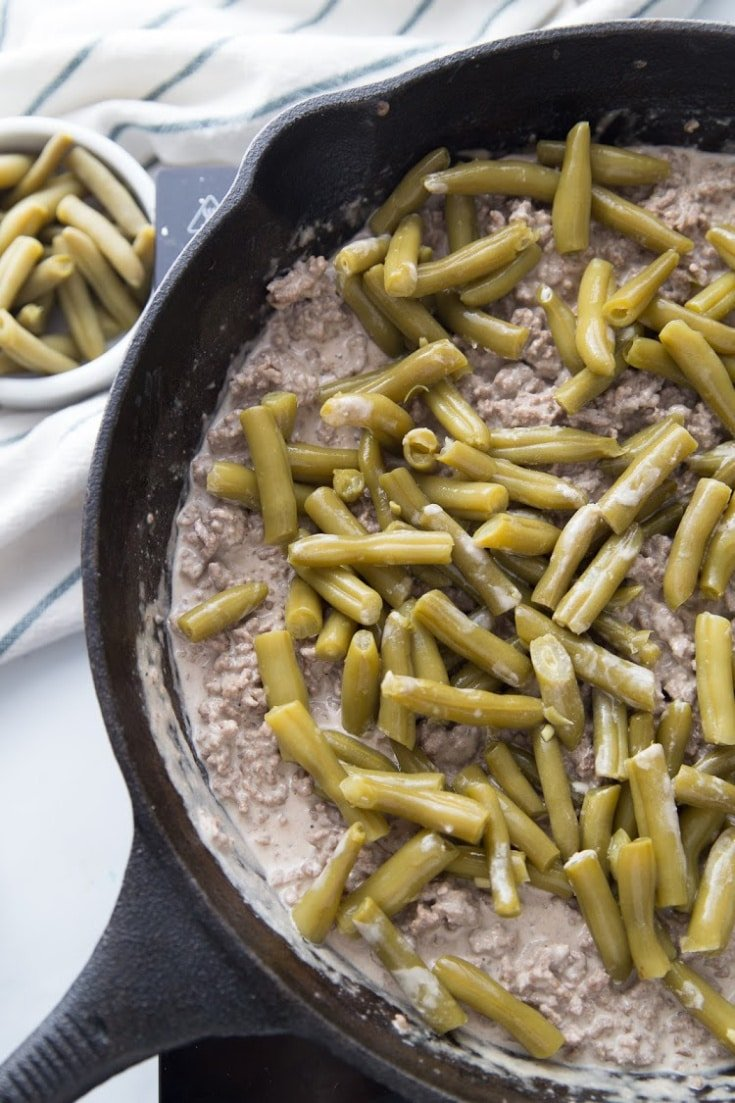 Keto Ground Beef recipe in a cast iron skillet with green beans on top process picture