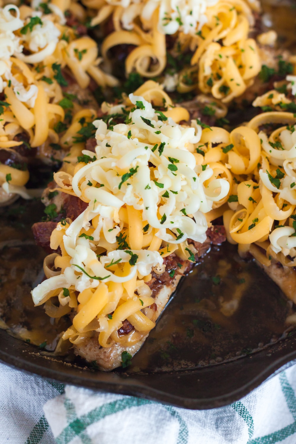 chicken breasts smothered in cheese in a cast iron skillet