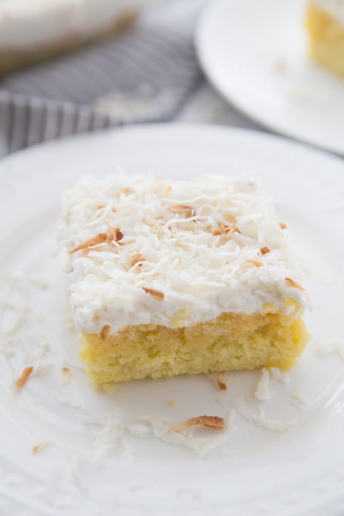 PIECE OF COCONUT CAKE WITH COCONUT DRIZZLED ON THE PLATE