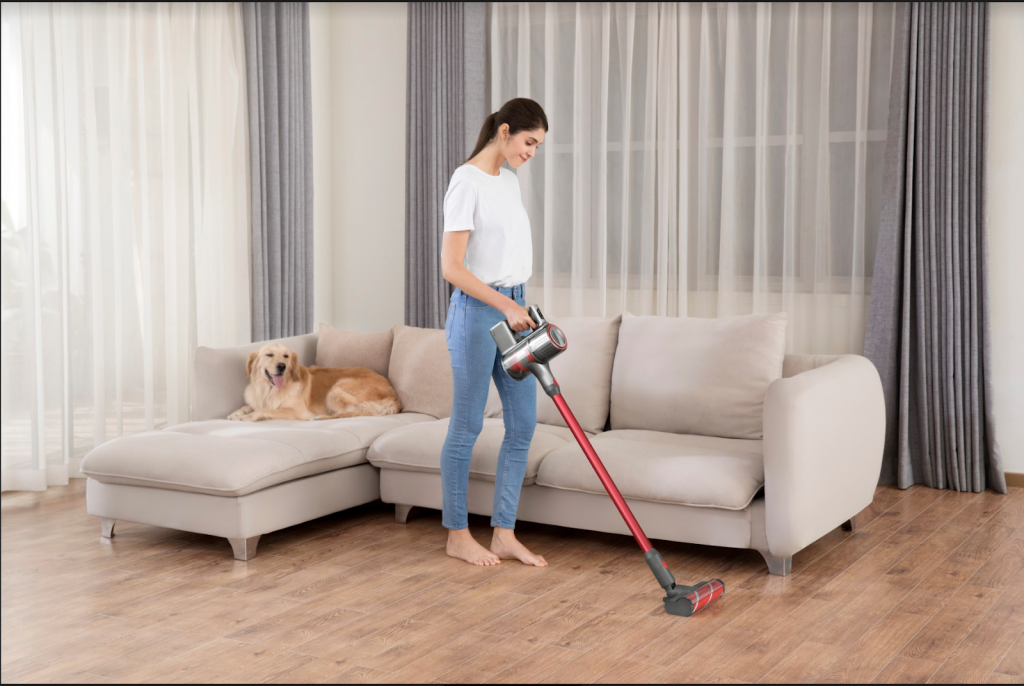 A Lady holding a vaccum in the living room with a sectional behind her and a dog on the couch.