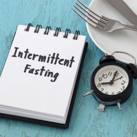 notepad with intermittent fasting written on it and a clock