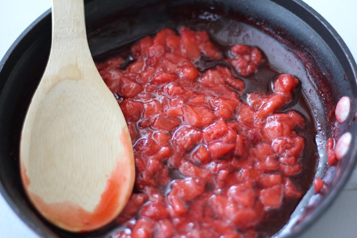 Low carb strawberry cheesecake topping being cooked down in a pan.
