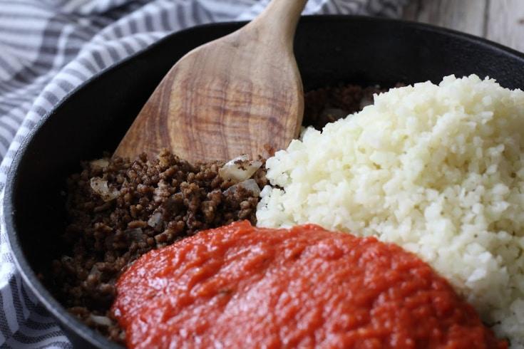 Ground beef, marinara, and cauliflower rice in cast iron skillet.