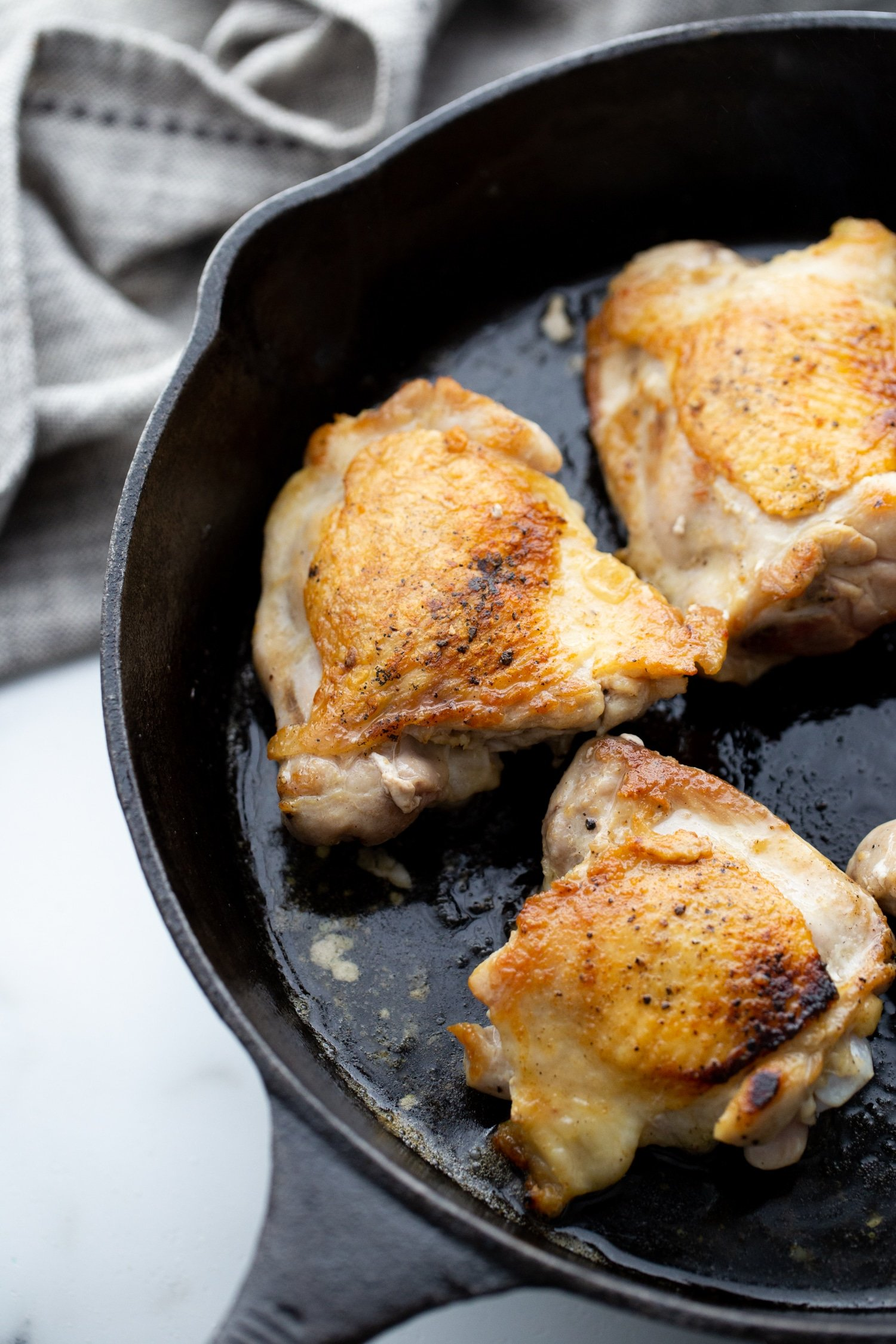 chicken thighs in a cast iron skillet seared
