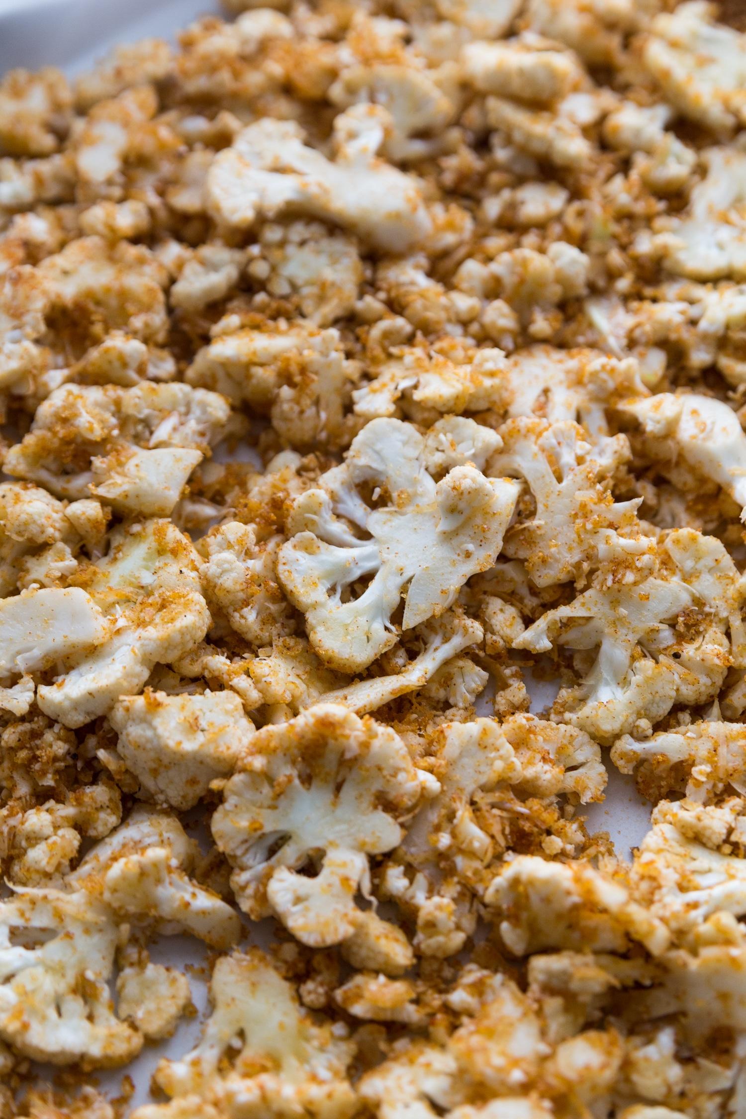 Cauliflower coated in a pork panko bread crumb mixture ans seasonings on a rimmed sheet pan.