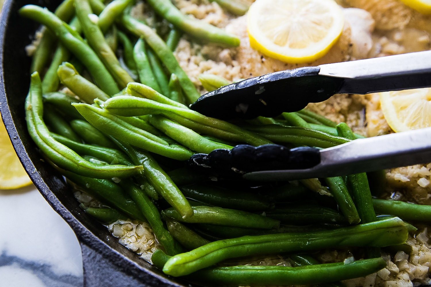 Steamed green beans being added to the riced cauliflower and chicken skillet.