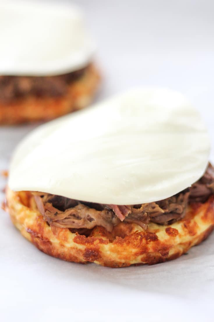 Keto Chaffle with roast beef and cheese on top for a keto French dip open faced sandwich