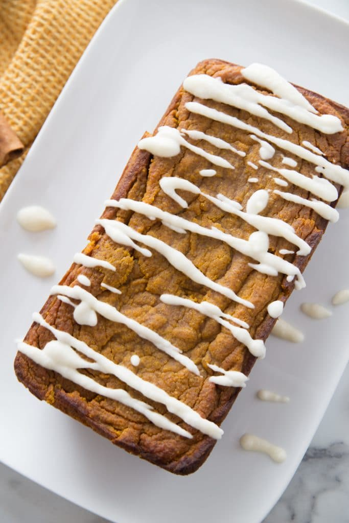 loaf of easy pumpkin bread recipe plated with glaze on top