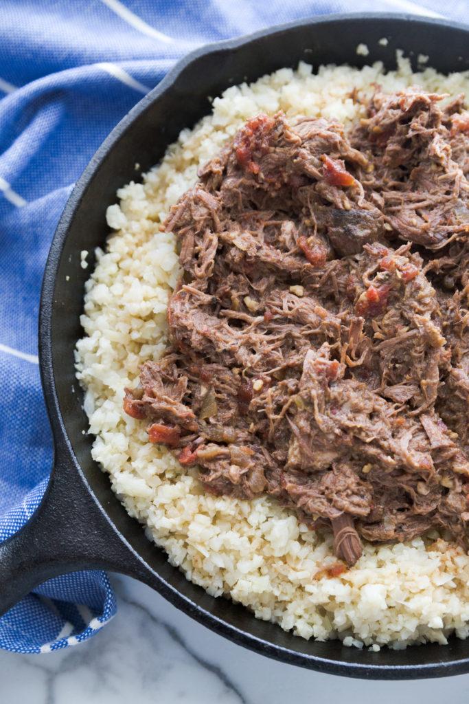 crock pot pot roast recipe served on cauliflower rice in a cast iron skillet