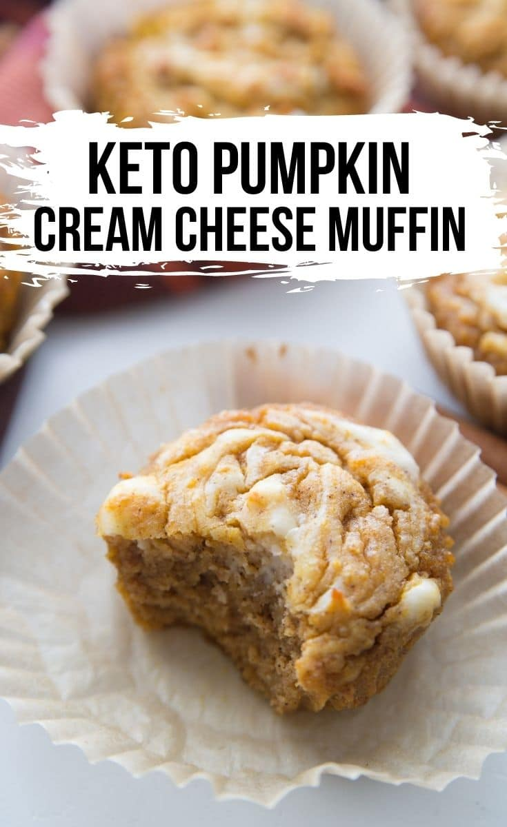 keto pumpkin cream cheese muffins with the muffin liner opened up and a bite taken out of muffin