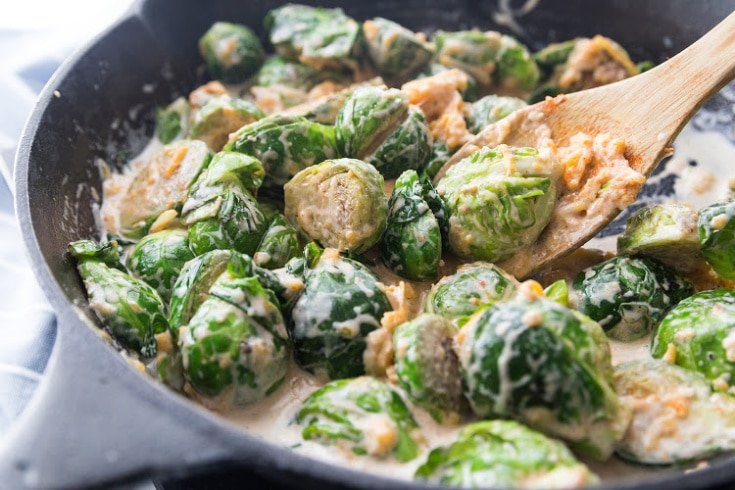 Brussels sprouts with cheeses and heavy whipping cream in a cast iron skillet