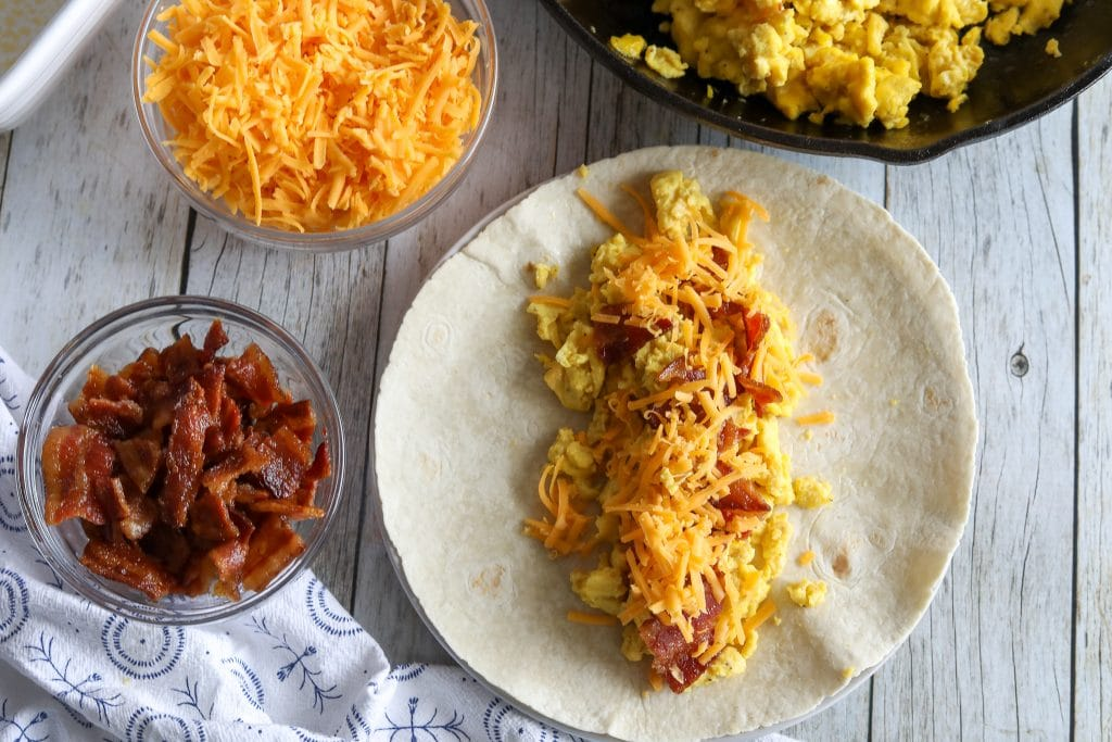 An overhead shot of how to assemble low carb breakfast burritos with cheese, eggs, and bacon.