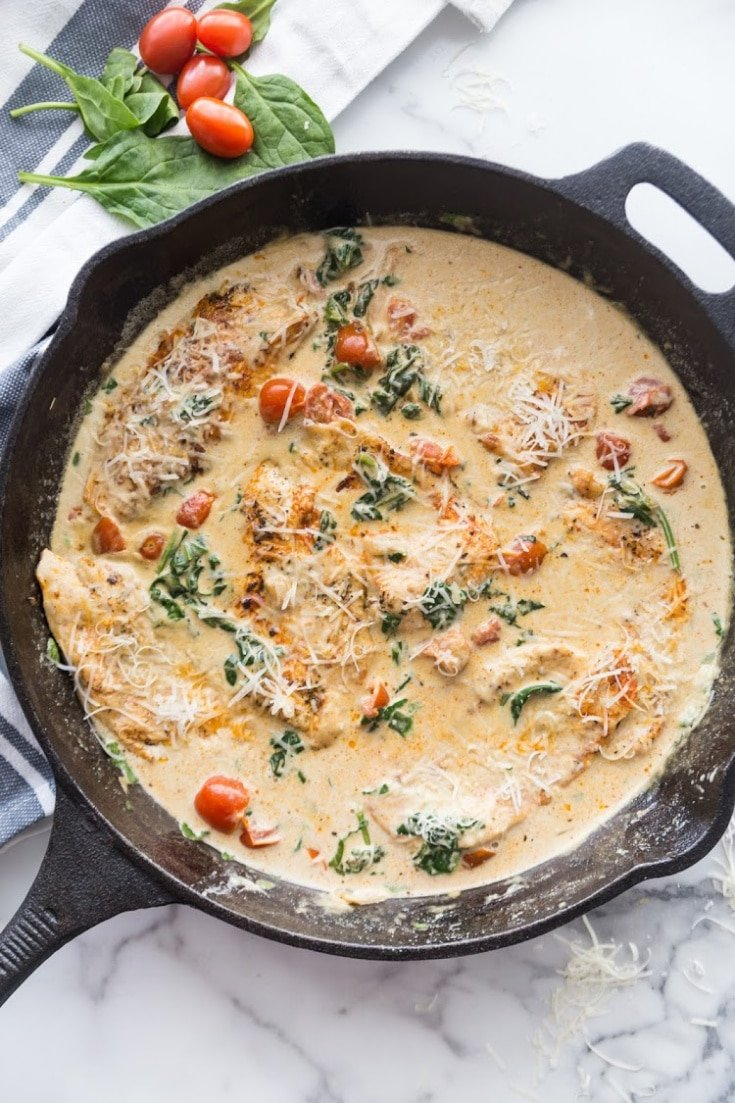 A cream sauce with chicken breasts, tomatoes and spinach in a skillet.