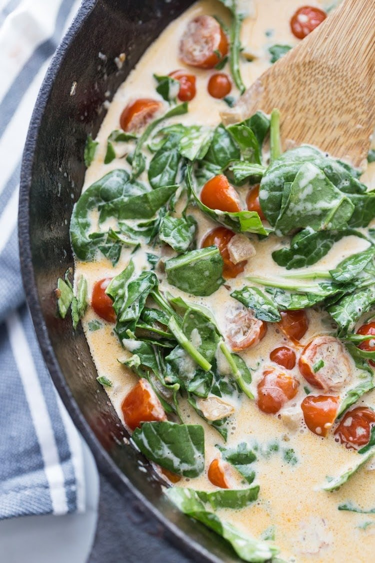 Skillet with sauteed spinach, cherry tomatoes and a garlic cream sauce.