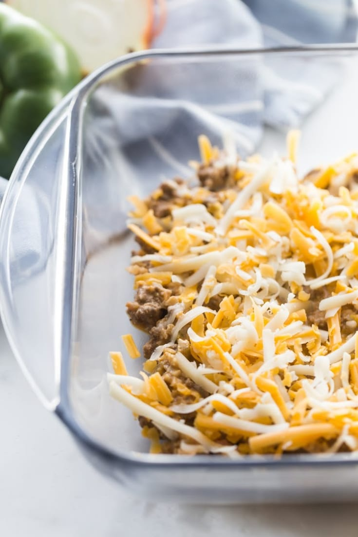 Glass casserole dish layered with ground beef and shredded cheese.