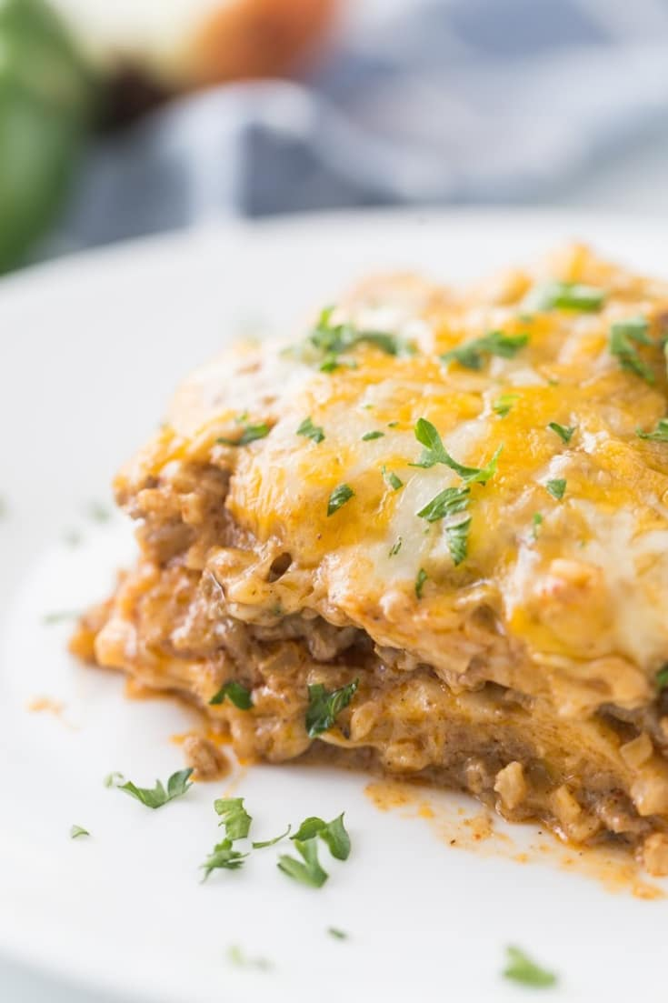 A large slice of taco bake casserole on a white plate topped with parsley.