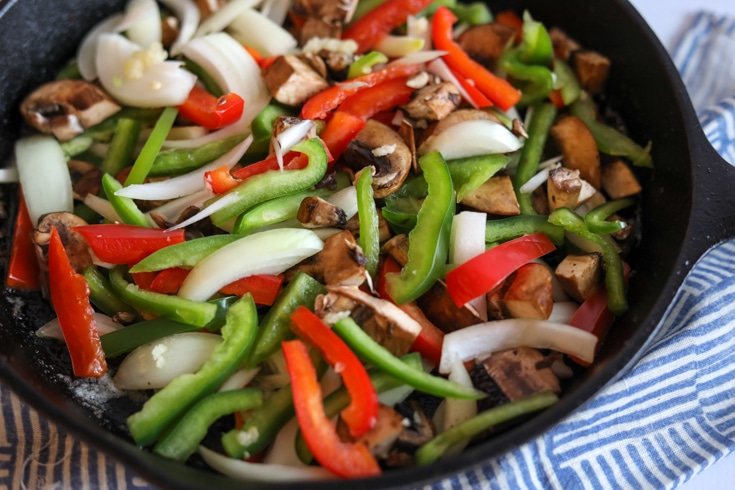 red and green peppers, onions and mushrooms in a skillet