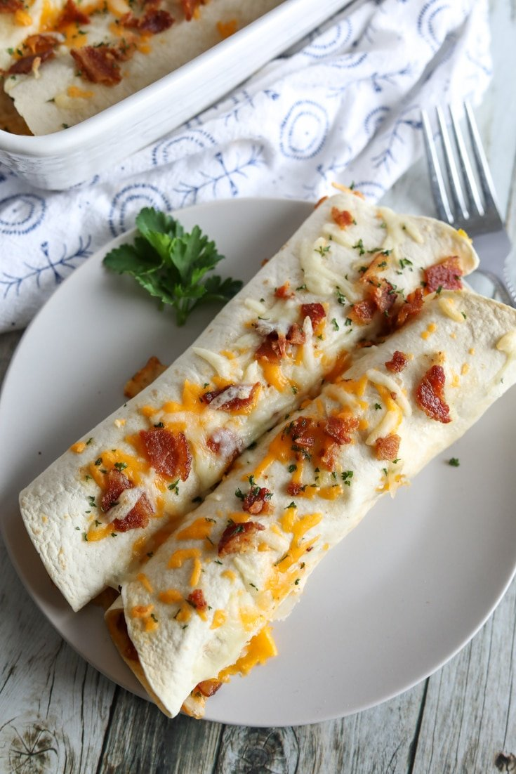 Two healthy low carb burritos on a plate with cheese and bacon on top.