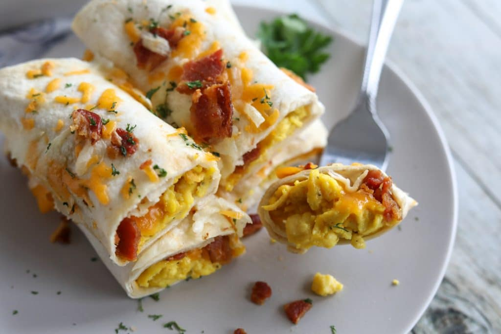low carb breakfast burrito on a plate cut in half with a bite on a fork