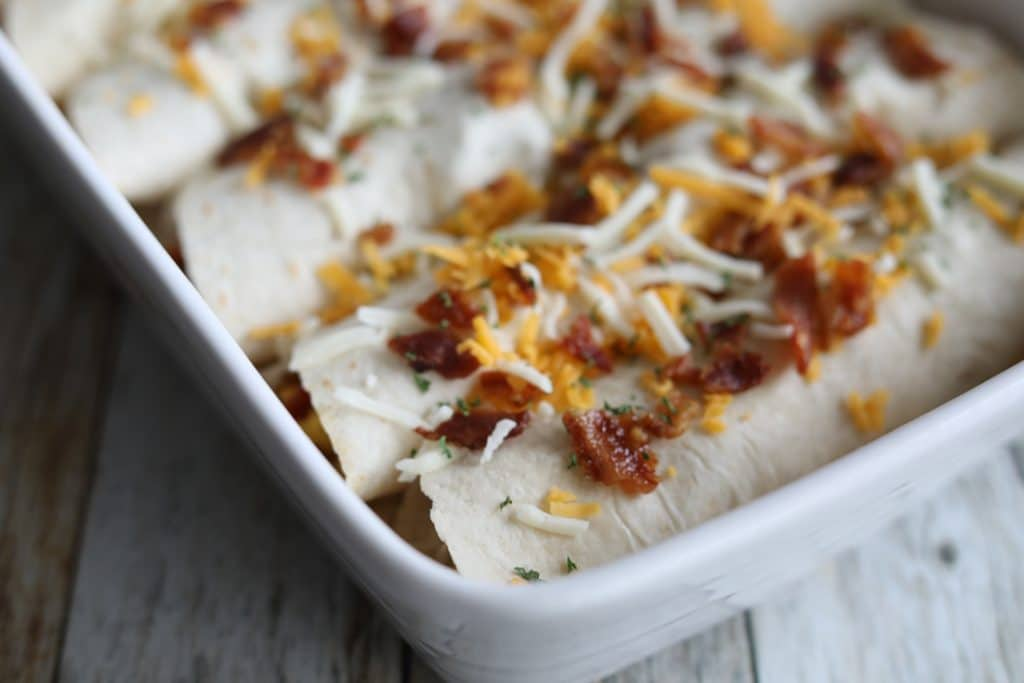 A side angle shot of a casserole dish filled with healthy low carb breakfast burritos.