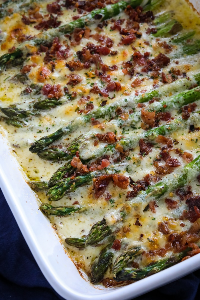 Cheesy keto asparagus casserole with crunchy bacon on top in a white pan.
