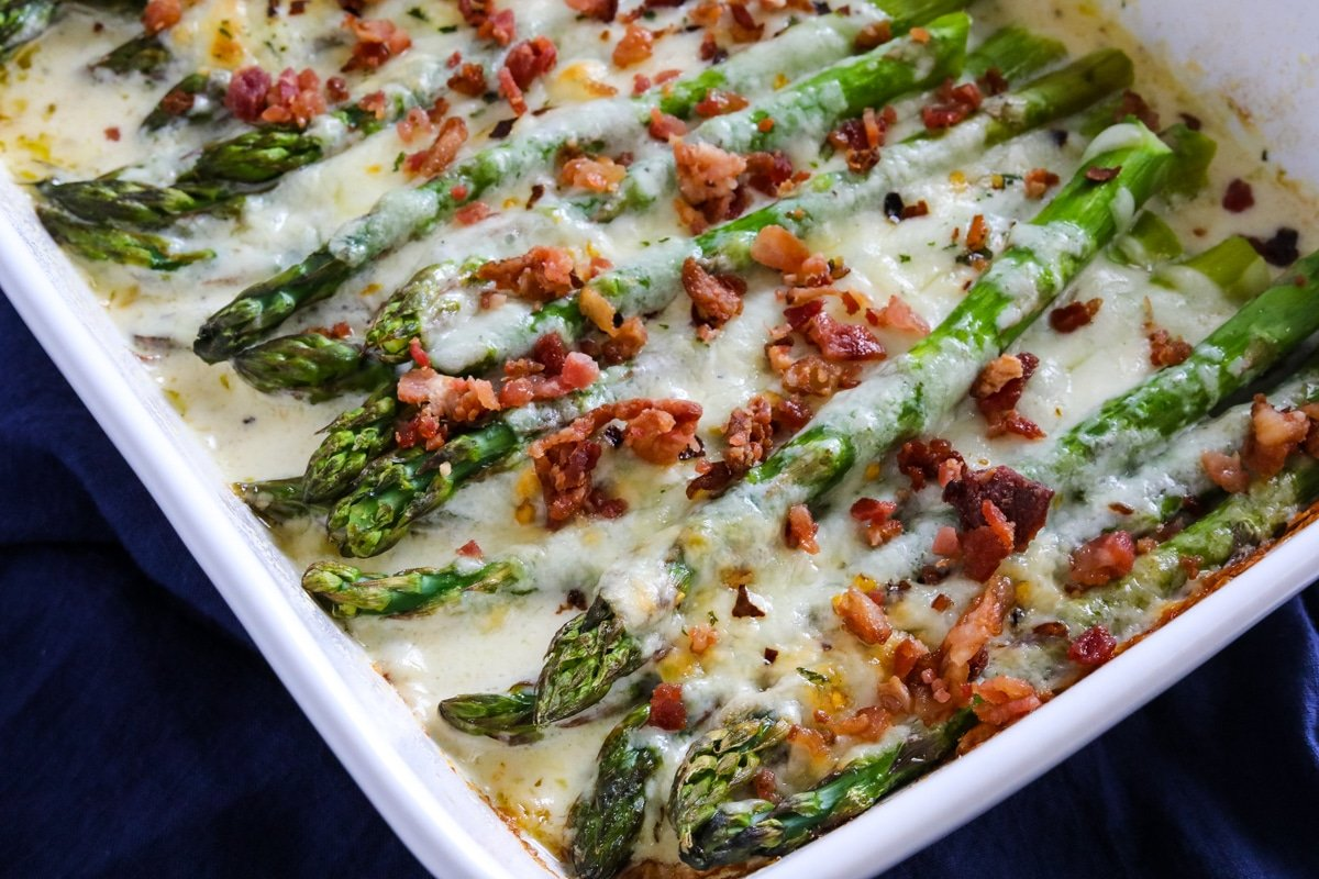 Cheesy asparagus casserole topped with bacon crumbles.