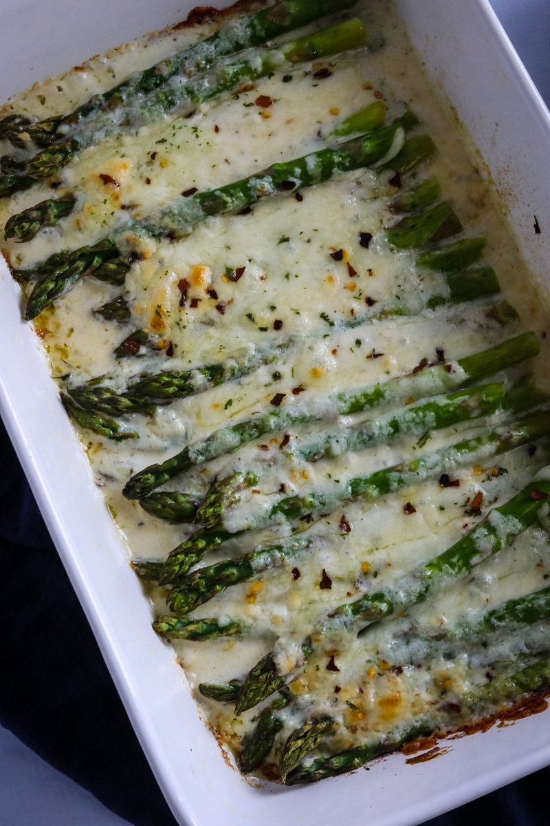 Baked cheesy asparagus casserole in a white pan.