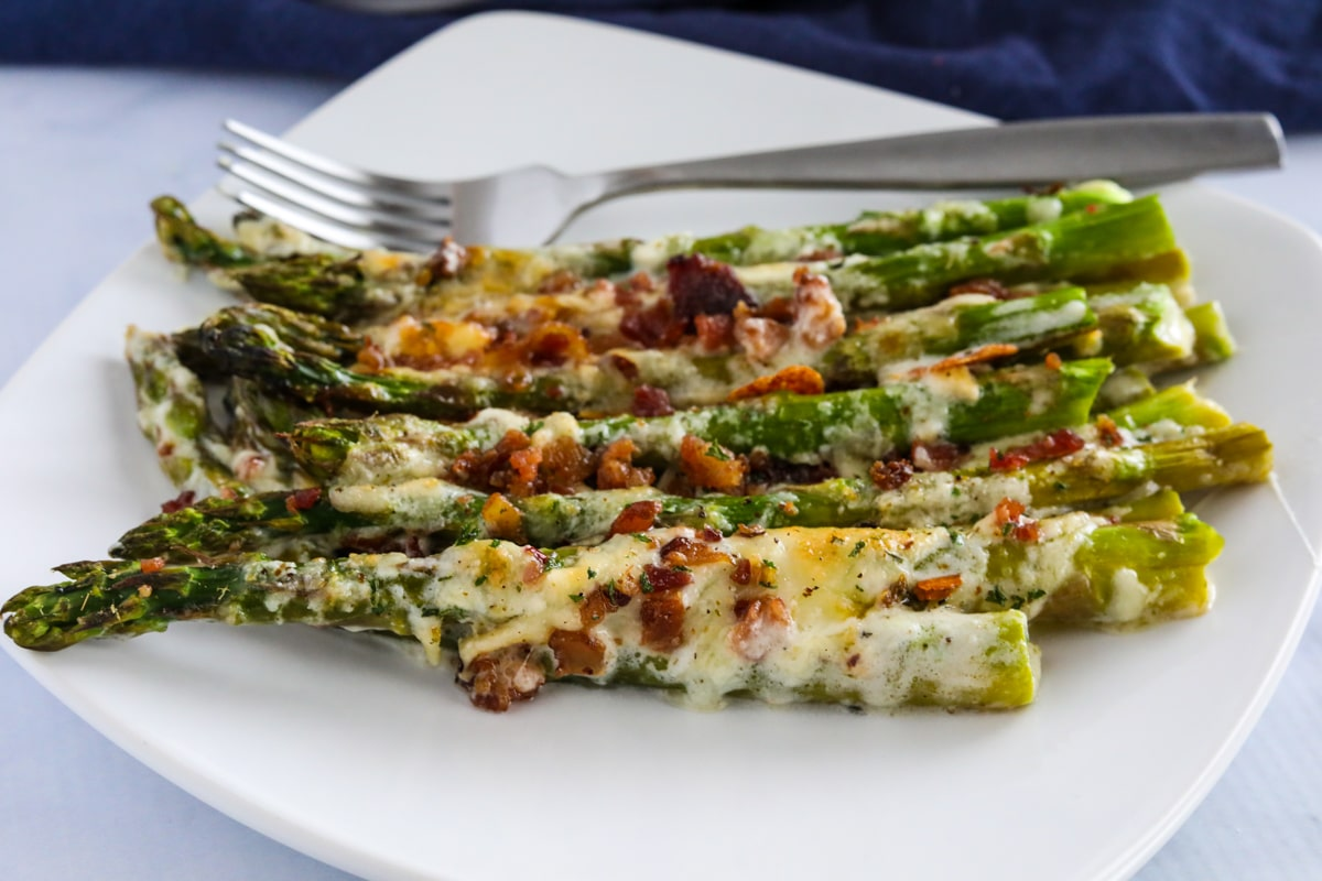 Keto asparagus casserole on a white plate, with a fork sitting behind it.