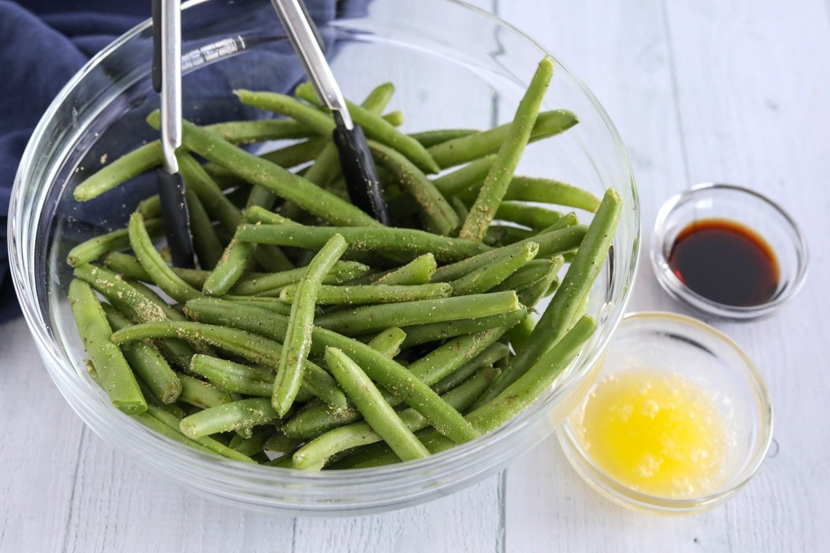 Fresh green beans, melted butter, and Braggs aminos in separate bowls