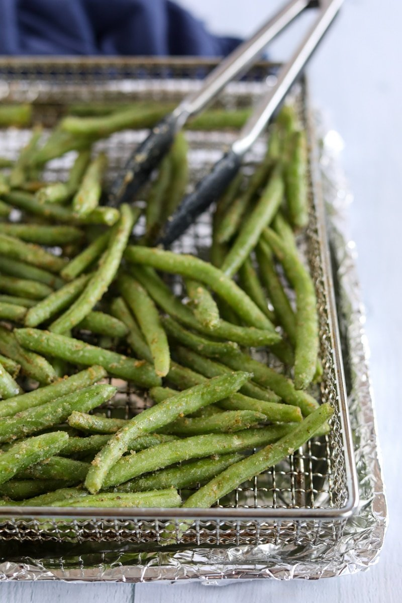 Fresh green beans in the air fryer basket with tongs in the back right corner.