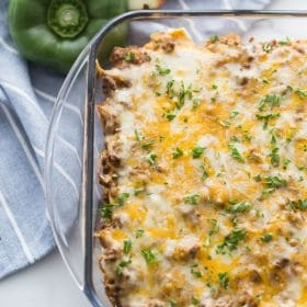 Mexican Taco Casserole in a Dish with green pepper behind it