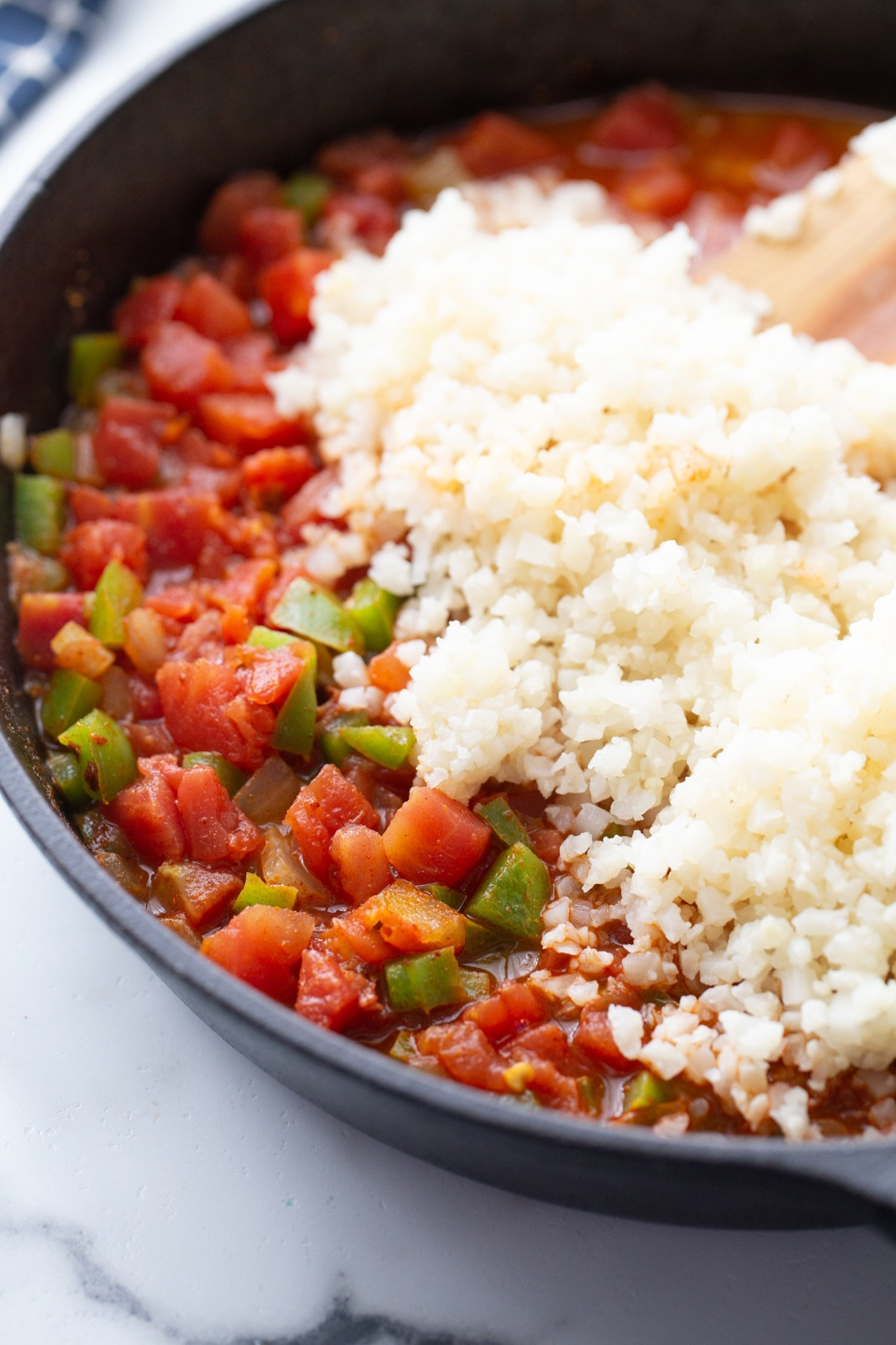 steamed riced cauliflower on top of the Rotel tomatoes in the skillet