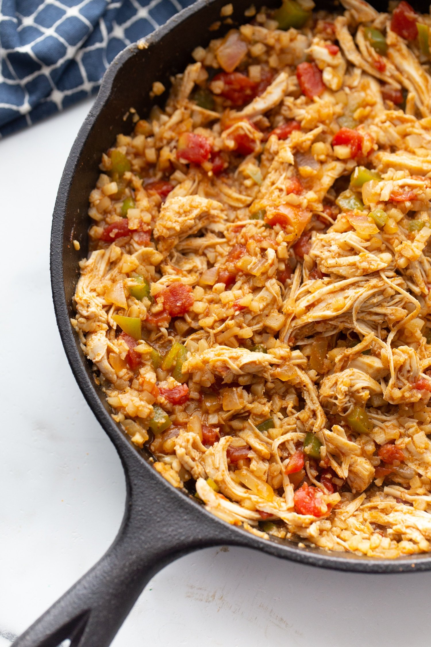 chicken, rotel, and cauliflower rice with taco seasoning in a skillet