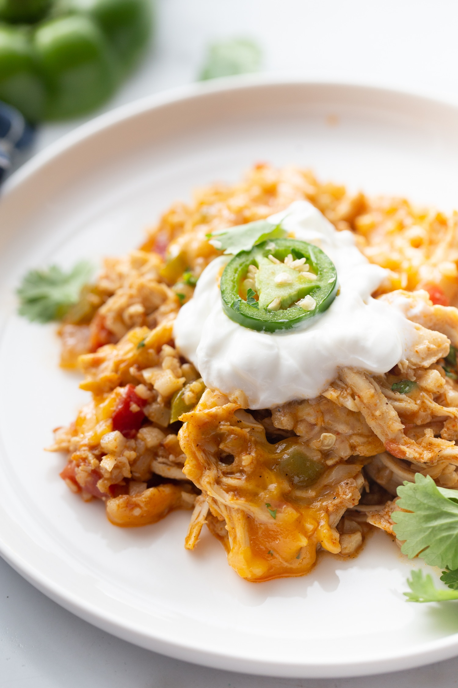 Keto Mexican Cheesy Chicken Skillet on a white plate with sour cream on top