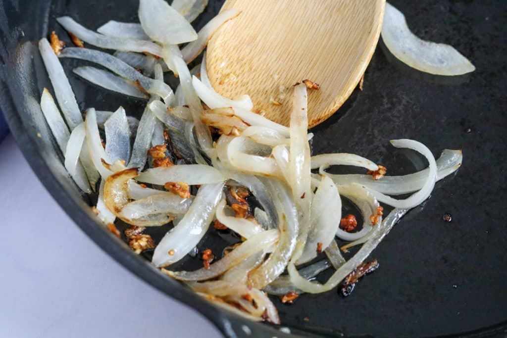 sliced onions and minced garlic in a cast iron skillet