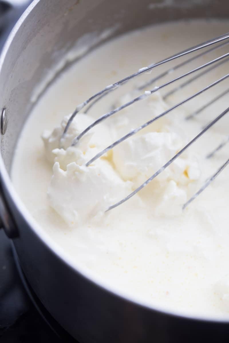 whisking cream cheese sauce in saucepan
