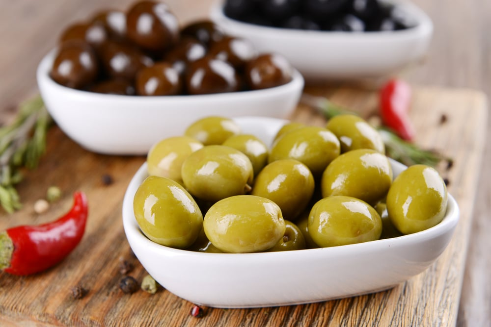 green and black olives in bowls on table