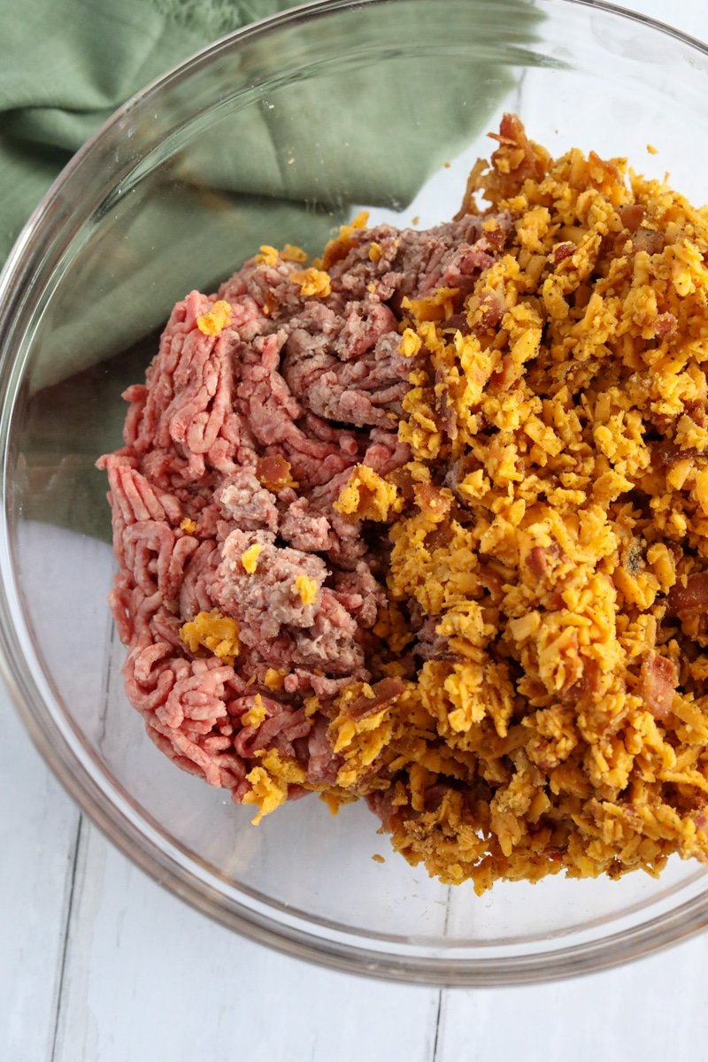 ground beef, cheese, spices and bacon in a clear bowl